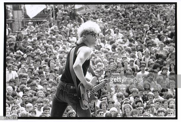 Photo of U2 and Adam CLAYTON, Adam Clayton performing on stage, audience