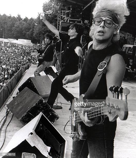 Photo of U2 and Adam CLAYTON and BONO and THE EDGE, Adam Clayton, Bono and The Edge performing on stage, audience, drink