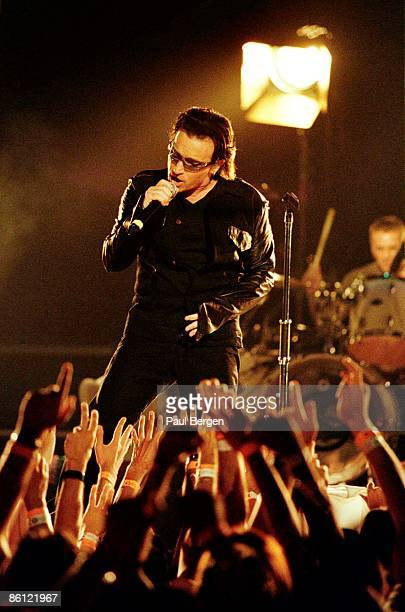 Photo of U2 and BONO and AUDIENCE; Bono performing live onstage on the 1st date of Elevation tour, showing fans in audience reaching out hands
