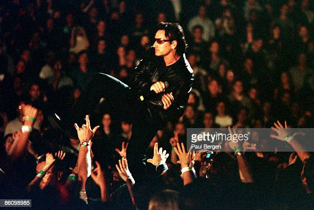 Photo of U2 and BONO and AUDIENCE Bono performing live onstage with audience reaching up hands on the 1st date of Elevation tour