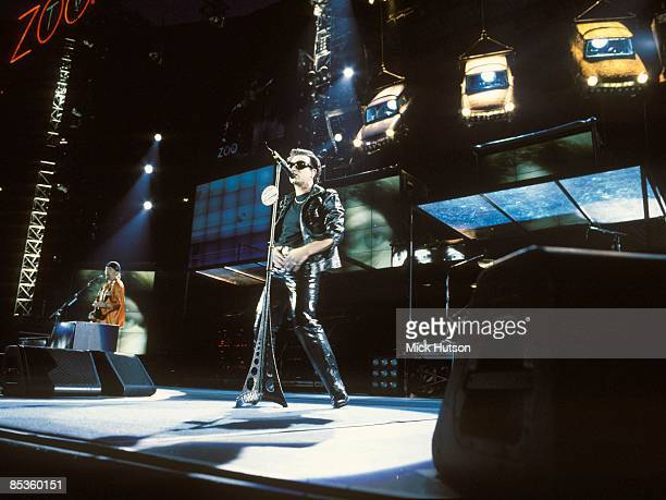 STADIUM Photo of U2 Bono performing live onstage on Zoo TV Zooropa tour with Trabant cars hanging from stage set