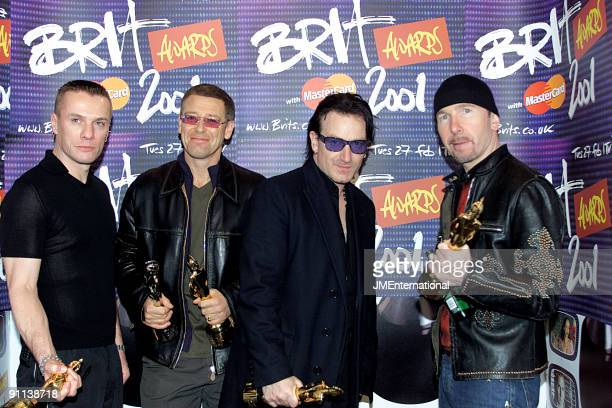 Larry Mullen Jnr Adam Clayton Bono The Edge posed group shot holding Brit awards