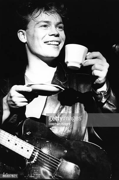 Photo of UB40 and Ali CAMPBELL Ali Campbell performing on stage drink tea cup