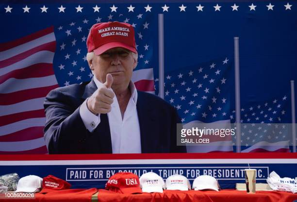 A photo of US President Donald Trump sits behind a table full of campaign hats as he speaks during a campaign rally at Florida State Fairgrounds Expo...