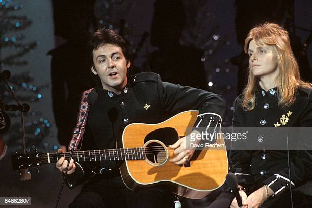 CENTRE Photo of WINGS and Linda McCARTNEY and Paul McCARTNEY with Linda McCartney in Wings performing on TV show playing acoustic guitar on Mike...