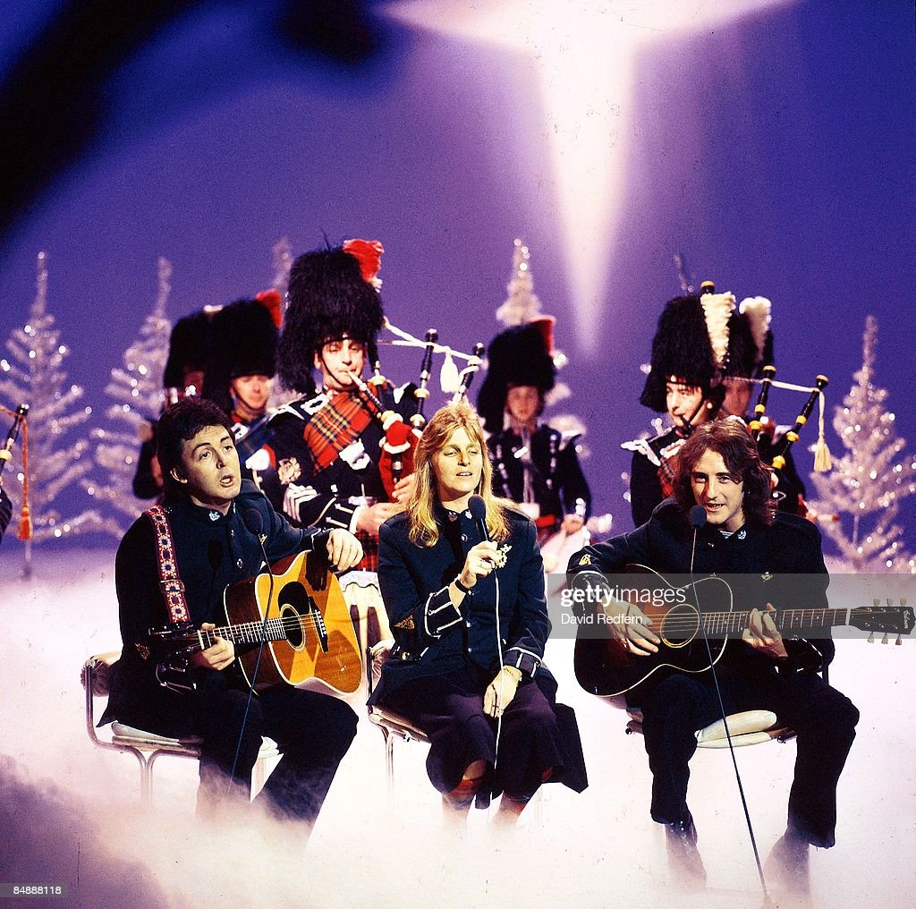 Photo of WINGS and Paul McCARTNEY and Linda McCARTNEY and Denny LAINE; L-R: Paul McCartney, Linda McCartney, Denny Laine, performing on Mike Yarwood Christmas Special, with bagpipe players (Campbeltown Pipes Band) and Christmas trees behind,