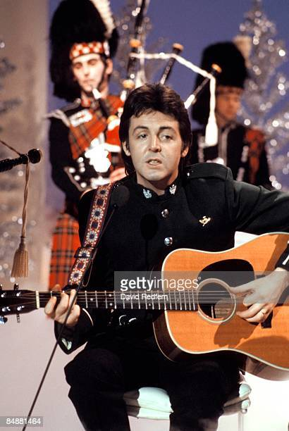 CENTRE Photo of WINGS and Paul McCARTNEY in Wings performing on TV show playing acoustic guitar with bagpipe players on Mike Yarwood Christmas Special