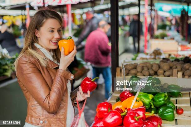 Photo of woman holding fresh bell pepper at the market. Vitamin, diet