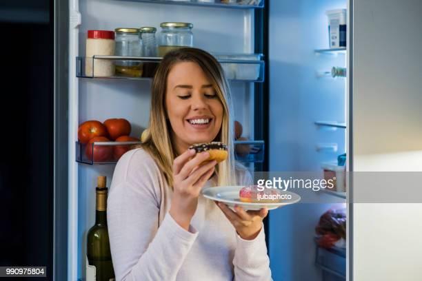 photo de femme avec des aliments sucrés près de réfrigérateur - frigo humour photos et images de collection