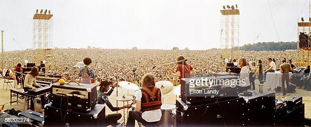 Photo of Woodstock Music & Arts Fair, panorama of festival stage and audience, with members of Joe Cocker's Grease Band onstage setting up for their performance, on August 17, 1969 in Bethel, New York. Drummer Bruce Rowland is centre.