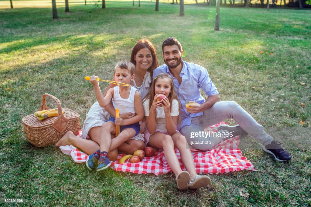 Photo of Young attractive  family blowing bubbles in the park : Stock Photo