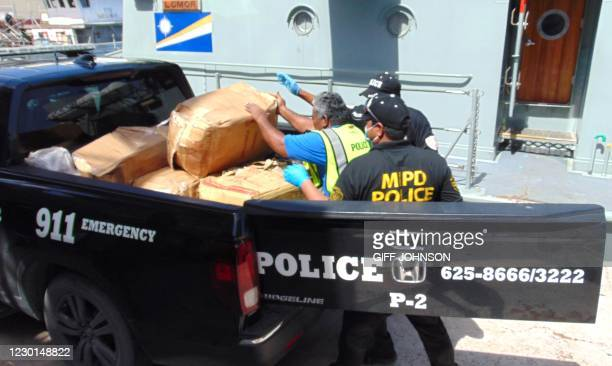 "Photo on December 15, 2020 shows Marshall Islands police loading a box filled with one-kilo ""bricks"" of cocaine into a police pickup truck from a..."