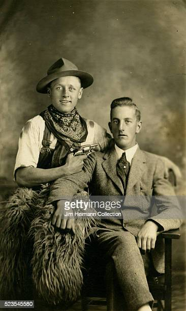 Photo postcard of a man in cowboy attire pointing a gun at a man in a suit as they both look at the camera