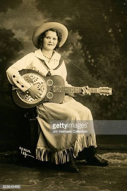 Photo postcard of a woman in traditional cowgirl attire holding a guitar