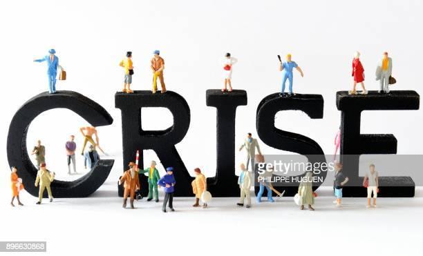 Photo prise le 07 août 2013 à Lille de figurines posées devant des lettres composant le mot 'crise' AFP PHOTO / PHILIPPE HUGUEN / AFP PHOTO /...