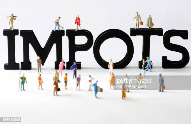 Photo prise le 07 août 2013 à Lille de figurines posées devant des lettres composant le mot 'impots' AFP PHOTO / PHILIPPE HUGUEN / AFP PHOTO /...