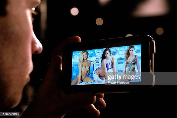A photo professional views the historic three covers of 2016 Sports Illustrated Swimsuit Issue on a smart phone on the streets of Midtown Manhattan...