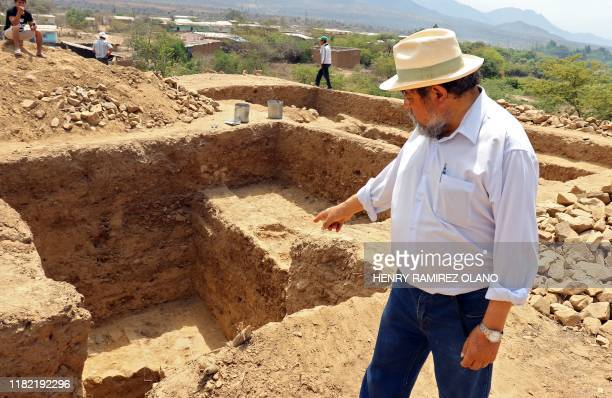 Photo released on November 13 2019 of Peruvian archaeologist Walter Alva pointing at excavations at the El Toro site where remains of a 3000yearold...