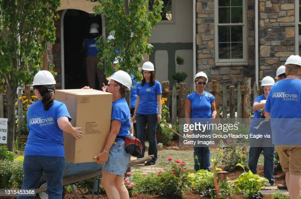 Photo Ryan McFadden Extreme Makeover Home Edition; volunteers unloading a tractor trailer of home items and furniture. Assembly line style