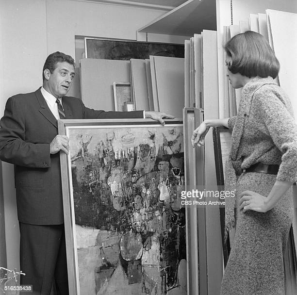 A photo shoot at the Raymond Burr Galleries 456 North Rodeo Drive Beverly Hills CA Raymond Burr pulls out a painting from the rack to show secretary...