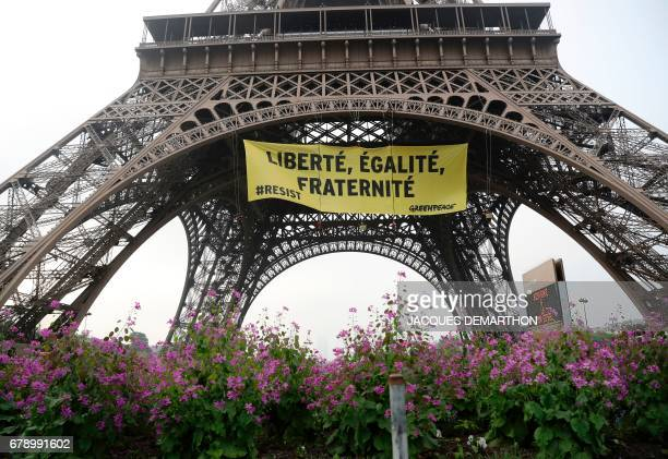A photo shows a banner reading 'liberty equality fraternity' hung by Greenpeace activists on the Eiffel Tower in Paris early on May 5 to protest...