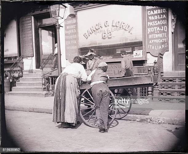 Photo shows a boy and a woman leaning on a pushcart belonging to a Mulberry Street huckster Photograph 1895