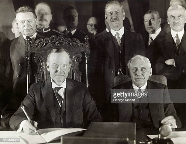 Photo shows a close up of President Calvin Coolidge and Secretary of State Frank B Kellogg signing the Kellogg multilateral treaty to outlaw war in...