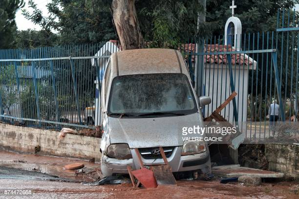A photo shows a damaged car in the town of Mandra northwest of Athens on November 15 after heavy overnight rainfall in the area caused damage and...