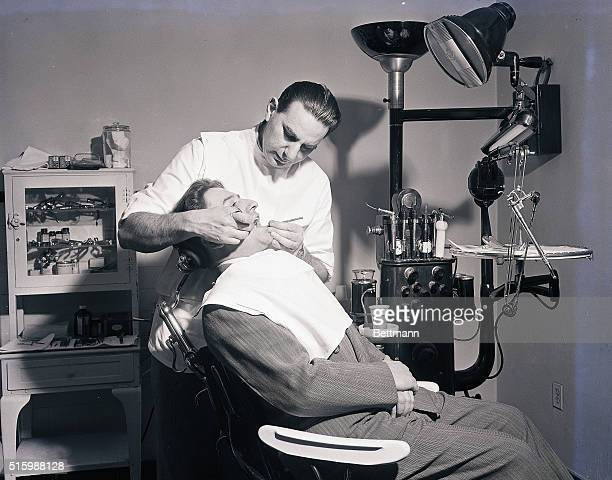 Photo shows a dentist working on a patient in the dentist's office Models CH Cohen DDS and Emil Romano the patient Ca 1940s1950s