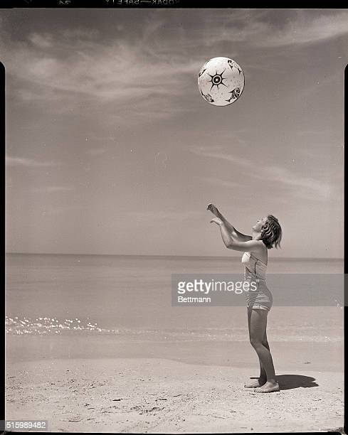 Photo shows a girl playing with a large ball on a beach Model Janet Boyette Duke