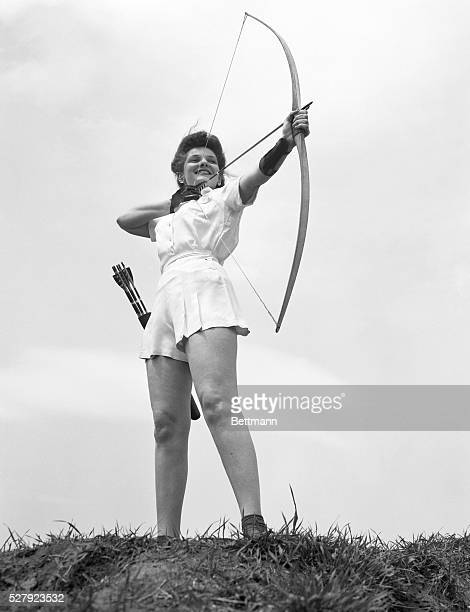 Photo shows a girl with a bow arrow and a quiver about to let an arrow fly Model Bernice Sherman Ca 1940s