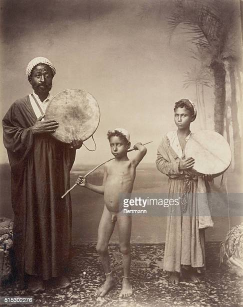 Photo shows a group of Arabic singers and dancers The man and girl are shown holding hand drums and the boy in the middle is naked Undated