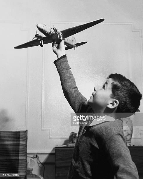 Photo shows a little boy in a room playing with a toy airplane as if it's in flight Ca 1930s