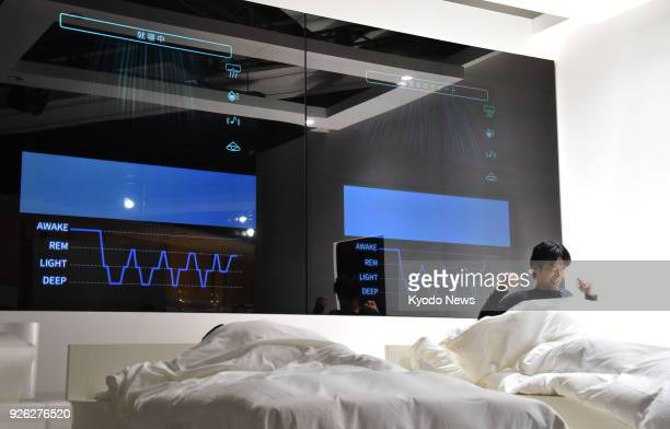 Photo shows a man lying in a room with a model of hightech beds and devices that would enable people to get quality sleep in Tokyo on March 1 in a...
