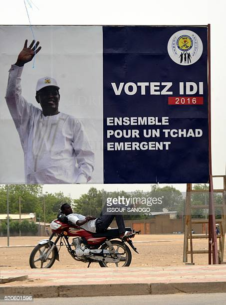 Photo shows a man resting under a campaign poster of Chad's president Idriss Deby Itno in N'djamena on April 12 2016 two days after Chad's...