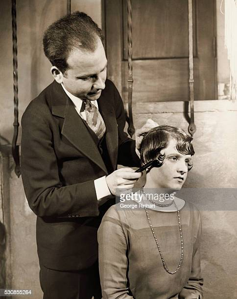 Photo shows a man standing behind a young woman and combing her hair Undated