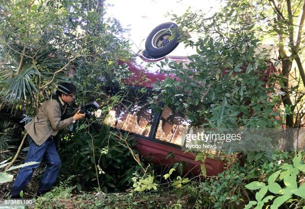 Photo shows a minibus that fell off a cliff five meters into the woods in Osaka the morning of Nov 12 2017 The bus carrying 18 mentally disabled...