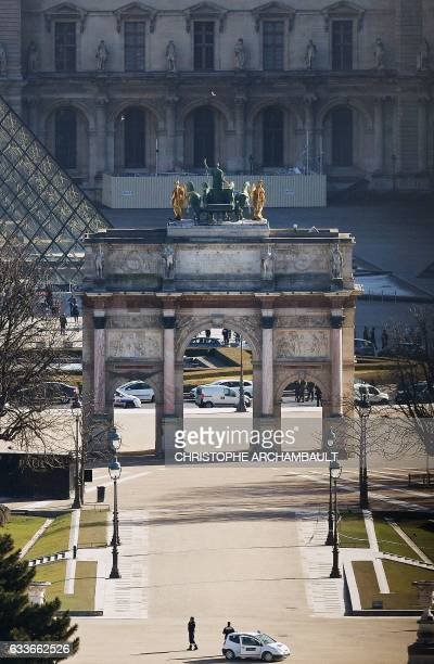 A photo shows a part of the Pyramid of the Louvre museum and the Arc de Triomphe of the Carrousel on February 3 2017 in Paris after a soldier...