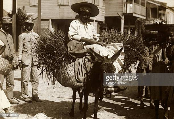 Photo shows a woman going to market with a load of country produce on a mule in PortAuPrince A couple of native policemen are seen in the background
