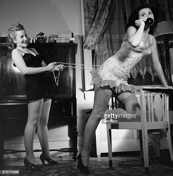Photo shows a woman in her underwear on the telephone while another similarly clad woman behind her tightens her corset. Undated photograph.