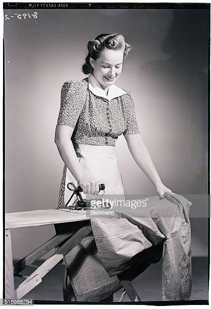 Photo shows a woman wearing an apron ironing a houndstoothprint shirt Model Patricia Garfield Ca 1930s
