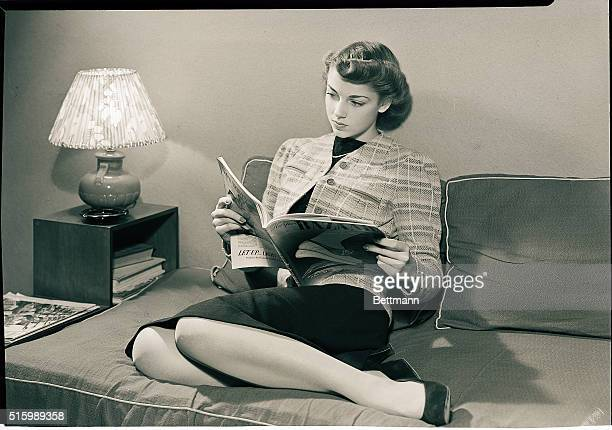 Photo shows a young girl reading Harper's Bazaar while seated on a couch. Model: Mary Loveland. Ca. 1940s-1950s.