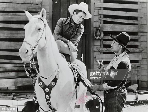 Photo shows actor John Wayne in a still from the movie 'Haunted Gold' in which a young Wayne is shown on a horse talking to a fellow cowboy Movie...