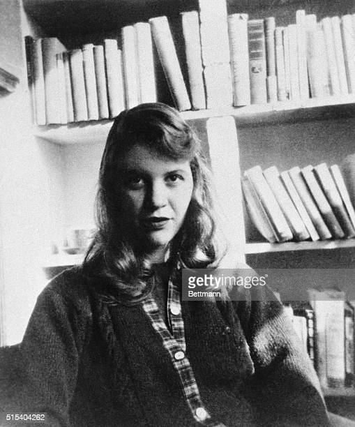 Photo shows author Sylvia Plath seated in front of a bookshelf