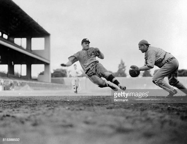 Photo shows Babe Ruth the home run king stealing home in one of the fast moments in his photoplay The camera stopped him in midair despite his...