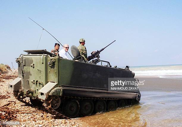 A 1999 photo shows billionaire businessman and former prime minister Najib Mikati as he rides on a Lebanese army armoured vehicle across the Awali...