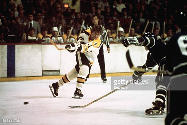 Photo shows Boston Bruin Bobby Orr in action on the ice having just shot the puck Behind him his teammates watch from the side bench