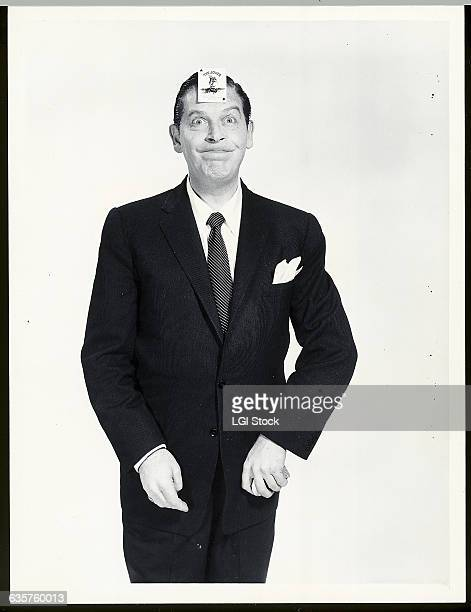 Photo shows comedian and actor Milton Berle in a funny pose with a joker playing card stuck to his forehead. Ca. 1950s.