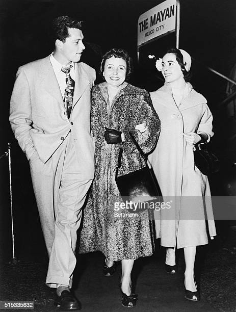 Photo shows Conrad Hilton Jr., wealthy hotel chain owner's sone, left, Mrs. Francis Taylor and her daughter Elizabeth Taylor upon their arrival from...