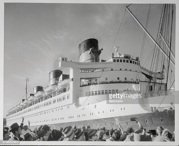 Photo shows crowd of on lookers waving to the passengers aboard the SS Queen Mary wishing them a safe Bon Voyage as the ship gets ready to depart...